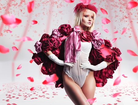 Beautiful blond beauty over flying rose petals photo