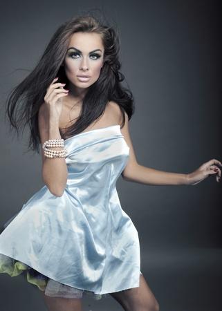 Beautiful brunette posing over studio background photo
