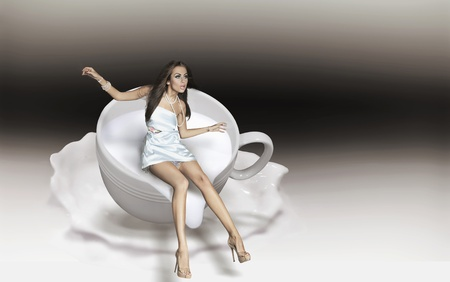 Dynamic photo of a young beauty in a cup of cappuccino Stock Photo - 8877825