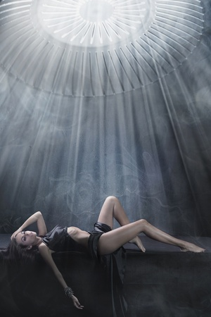 Attractive brunette lying in a dark chamber photo