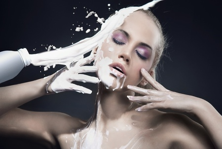 Portrait of a beautiful blonde dousing with cream photo