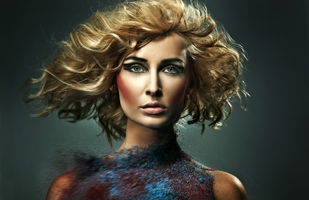 Young blonde beauty and flecks of colored sand photo