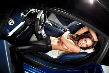 mujer desnuda sentada: Sexy mujer sentada en un coche deportivo