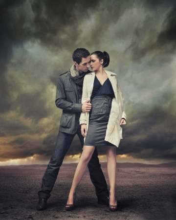 Handsome couple posing over stormy background photo