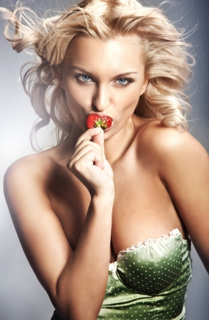 Young lady eating a strawberry photo