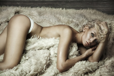Beautiful blonde beauty on a carpet photo