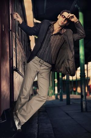 An elegant man next to a train photo
