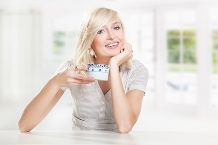 Young cute blonde drinking coffee Stock Photo - 9064727