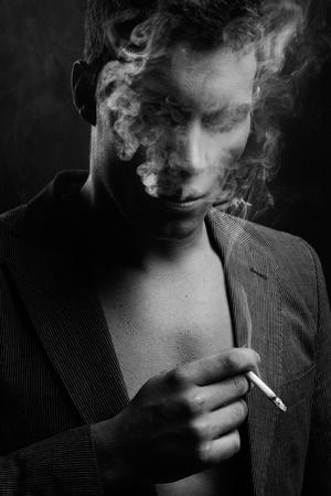 Cute guy smoking a cigarette photo