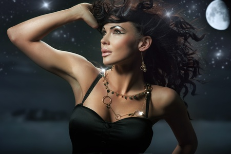 Fashionable brunette over starry night background photo