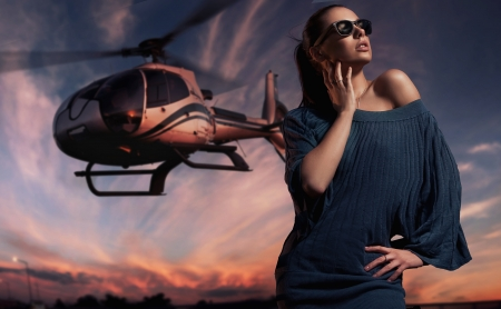 fashionable lady wearing sunglasses with helicopter in the background photo