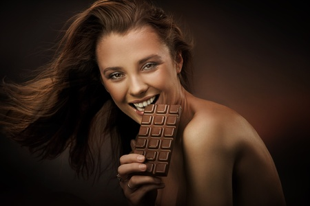 Cheerful woman eating chocolate photo
