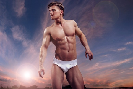Young handsome muscular guy over twilight sky photo