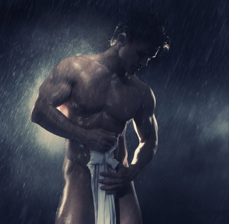 Young handsome athlete standing in the rain photo