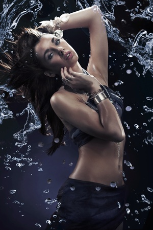 Young beauty dancing with water splash photo