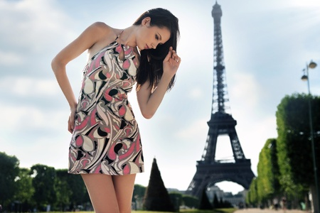 Young brunette posing over Eiffel tower background Stock Photo