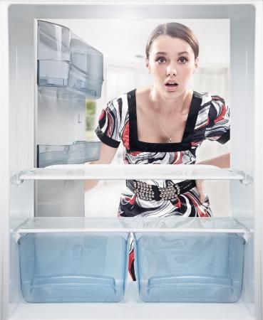 frigo: Jonge vrouw op zoek op lege plank in de koelkast. Stockfoto