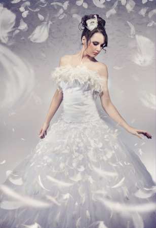 Beautiful bride posing over white flying feathers photo