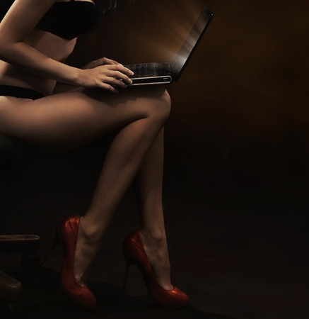 Woman wearing lingerie with laptop photo