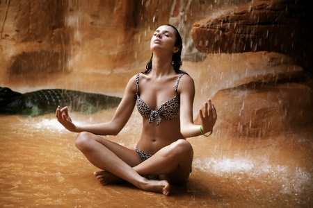 Young woman doing yoga exercise under waterfall photo