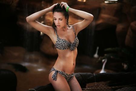 wet women: Pretty brunette relaxing next to a tropical waterfall Stock Photo