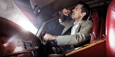 wine road: Handsome man drinking in the car