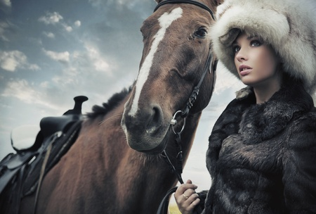 Nostalgic young brunette posing next to a horse Stock Photo - 9077693