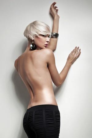 mujer rubia desnuda: Rubia desnuda junto a una pared blanca Foto de archivo