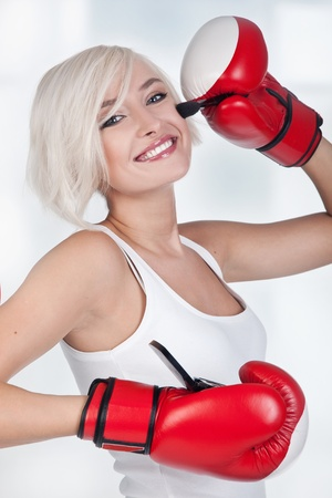 Cheerful blond woman doing make up in boxing gloves photo