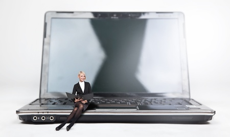 Young businesswoman sitting on a laptop, isolated on white photo