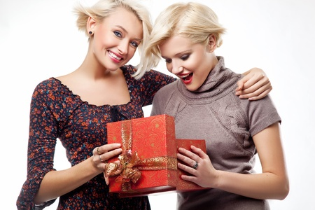 beauties: Two smiling blond beauties holding a christmas present