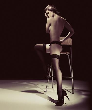 mujer desnuda sentada: Joven atractiva en la silla
