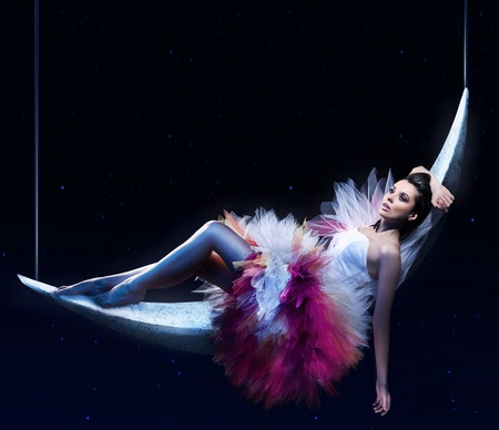 Beauty brunette lying on the crescent moon photo