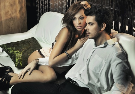 vogue: Young sexy pair posing on the white couch