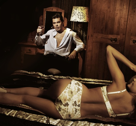 sexual intimacy: Handsome man with glass of wine with smiling girl in lingerine
