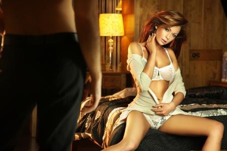 parejas sensuales: Linda Morena en lingerine sentada en la cama y a la espera de un hombre Foto de archivo