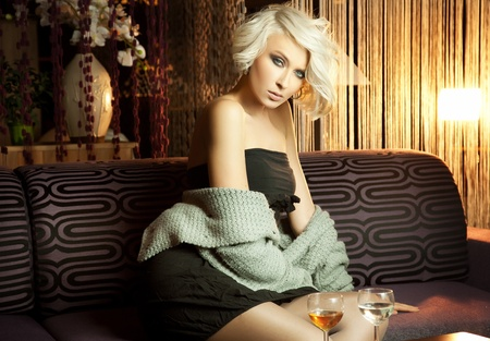 Beautiful sexy blond girl sitting on the couch and posing  photo