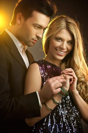 gifting: Joven feliz haciendo un anillo a una joven y bella mujer
