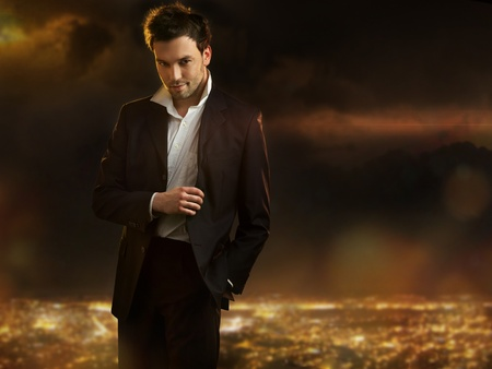 Elegant young handsome man over night city background photo