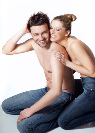 embraces: Happy young couple in casual clothing, white background