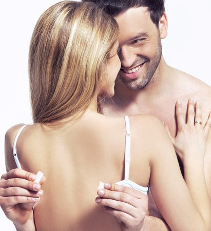 handsome man is unfastening the bra for the woman  photo