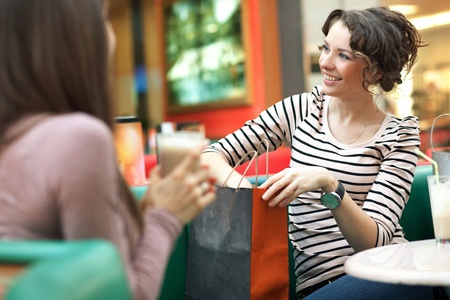 coffee shop: Stunning women after shopping talking with friend Stock Photo