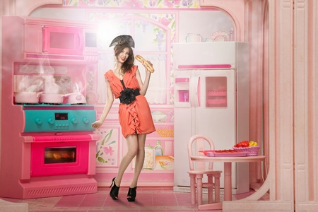 Young woman like a doll cokking in pink kitchen