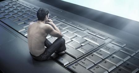 sad man: Foto conceptual de un joven adicto a la internet Foto de archivo