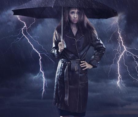 Single woman wearing coat holding umbrella. Creative szmbol of the bad weather Stock Photo - 9512910