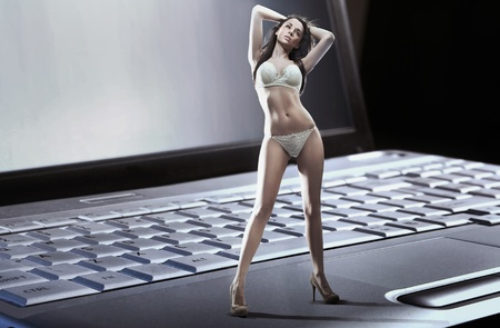 Sexy woman wearing lingerie standing n laptop photo