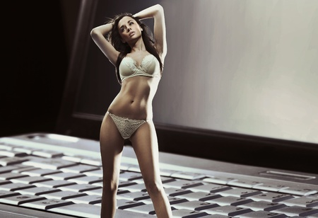 Beautiful woman in lingerie with laptop screen in background photo