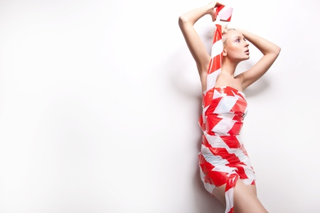 Beautiful young blond woman wrapped in warning tape