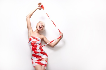 Screaming young beauty is wrapping up with warning tape  Stock Photo - 9512852