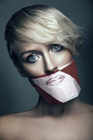 imbavagliare: Foto concettuale di donna con la bocca nastrate  Archivio Fotografico